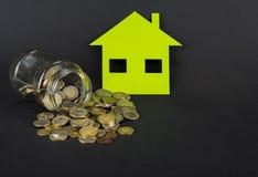 Het groene huis bespaart geld Een kruik met euro of dollar stock foto