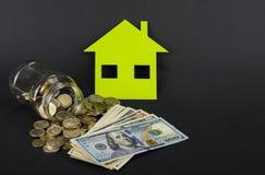 Het groene huis bespaart geld Een kruik met euro of dollar royalty-vrije stock afbeeldingen