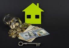 Het groene huis bespaart geld Een kruik met euro of dollar stock afbeeldingen