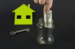 Het groene huis bespaart geld Een kruik met euro of dollar royalty-vrije stock foto