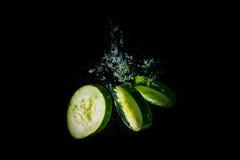 Het groene komkommer abstracte bespatten in het duidelijke blauw Stock Foto