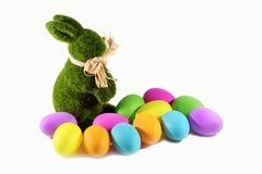 Het groene konijn van het graskonijntje met de kleurrijke eieren van Pasen Stock Foto