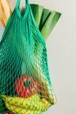 Het groene koord het winkelen zak hangen op een haak in de keuken stock afbeeldingen