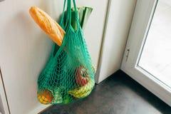 Het groene koord het winkelen zak hangen op een haak in de keuken royalty-vrije stock afbeelding