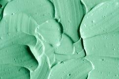 Het groene kosmetische klei gezichtsmasker, room, lichaam schrobt textuur dichte omhooggaande, selectieve nadruk Abstracte achter stock afbeeldingen