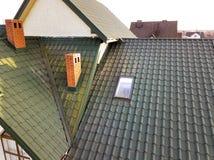 Het groene metaal shingled huisdak met zolder plastic venster en baksteenschoorsteen royalty-vrije stock afbeeldingen