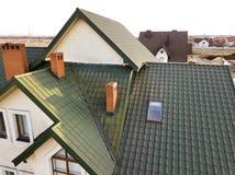 Het groene metaal shingled huisdak met zolder plastic venster en baksteenschoorsteen stock foto's
