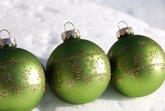Het groene ornament van Kerstmis op sneeuw stock foto