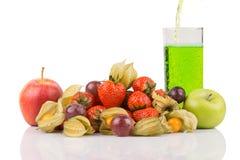 Het groene sap inschenken aan de rode en groene appelen van glasbehide met oranje physalis, purpere druiven en rode aardbeien op  Royalty-vrije Stock Afbeeldingen