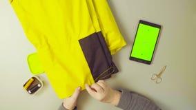 Het groene scherm Handen van oude vrouwen naaiende broek stock footage