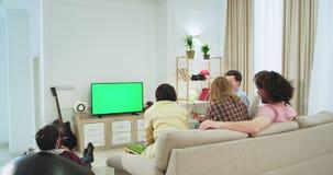 Het groene scherm op de grote groep van TV vrienden op de bank in een grote ruime woonkamer die op iets op TV letten, multi stock video