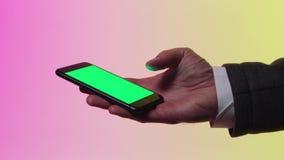 Het groene scherm op mobiel voorraad De holdingstelefoon van de zakenman` s hand met het groene scherm stock footage