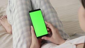 Het groene scherm op mobiele telefoon van jonge vrouw in bed thuis voor chromasleutel stock footage