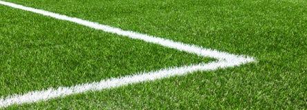 Het groene synthetische kunstmatige sportterrein van het grasvoetbal met de witte lijn van de hoekstreep stock afbeeldingen