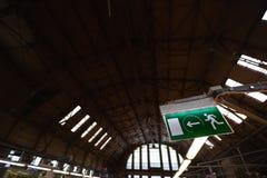 Het groene teken van de nooduitgangweg in een mooi industrieel omringend binnenland - Bouw van een hangaar royalty-vrije stock foto's