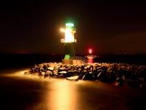 Het groene vuurtoren shinning aan het eind van steenachtige pijler in donkere nacht Stock Foto's