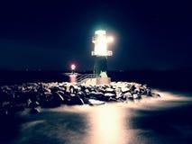 Het groene vuurtoren shinning aan het eind van steenachtige pijler in donkere nacht Stock Afbeelding