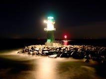 Het groene vuurtoren shinning aan het eind van steenachtige pijler in donkere nacht Royalty-vrije Stock Afbeeldingen