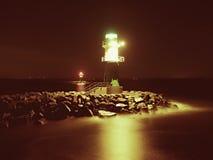 Het groene vuurtoren shinning aan het eind van steenachtige pijler in donkere nacht Royalty-vrije Stock Foto's
