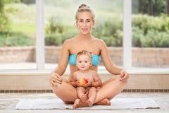 Het groepsportret van witte Kaukasische moeder en babydochter die de yoga die van fysieke geschiktheidsoefeningen samen doen in l Stock Foto