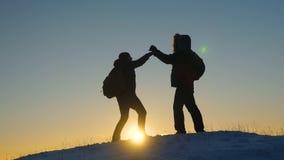 Het groepswerk is beste van beste reizigers de toeristen met komen in de winter samen bovenop een heuvel in stralen van zon Klimm stock videobeelden