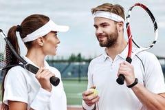 Het groepswerk maakt het Werk van de Droom Twee tennisspelers op het hof glimlachen aan elkaar royalty-vrije stock afbeeldingen