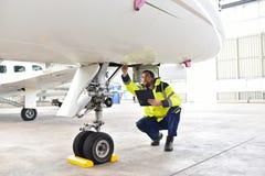 Het grondpersoneel bij de luchthaven controleert het hydraulische systeem van Th royalty-vrije stock afbeeldingen