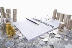 Het grootboek van de boekhouding tussen stapels van muntstukken Stock Foto's