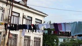Het grote aantal van gewassen wasserij hangt op een kabel en droogt op de straat dichtbij het huis stock footage