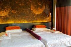 Het grote bed van de koningsgrootte in decoratieve humeurige ruimte stock afbeeldingen