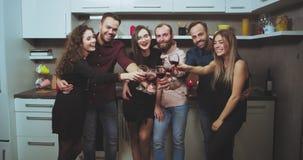 Het grote bedrijf van jonge kerels en dames heeft een partij van de huiswijn zij die recht aan de camera glimlachend larg kijken  stock videobeelden