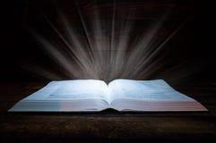 Het grote boek van de Bijbel ligt op een houten lijst In dark Een licht glanst hierboven op het boek van Het licht komt het boek  royalty-vrije stock foto