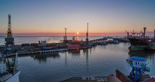 Het grote die schip met sleepboten wordt gevolgd gaat de haven op zonsopgang in Een industriële zeehaventerminal met ladingskrane stock footage