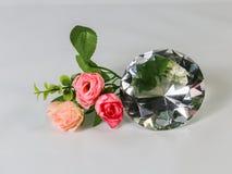 Het grote duidelijke kristal van de diamantvorm met rozen, concept voor Valentin Stock Foto's