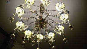 Het grote elegante glanzende kroonluchter hangen op het plafond stock videobeelden