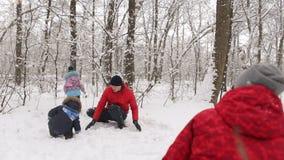 Het grote gelukkige familie spelen met sneeuw in de winterpark stock videobeelden