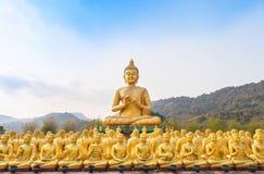Het grote gouden standbeeld van Boedha en vele kleine gouden standbeelden van Boedha in tempel nakornnayok Thailand royalty-vrije stock fotografie