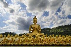 Het grote gouden standbeeld van Boedha onder vele kleine standbeelden van Boedha Stock Fotografie