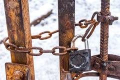 Het grote hardwarehangslot met een dikke metaalketting weegt op de ijzerdeur De ijzerpoort in de binnenplaats op het grote slot w Royalty-vrije Stock Afbeeldingen