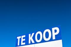 Het grote Nederlands voor verkoopteken voor een blauwe hemel Stock Fotografie