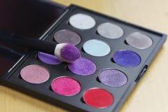 Het grote oogschaduwpalet van vele kleurenschaduwen in lilac, violette en rode tonen, met maakt omhoog borstel van helder lilac p stock foto