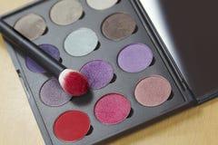Het grote oogschaduwpalet van vele kleurenschaduwen in lilac, violette en rode tonen, met maakt omhoog borstel van helder rood po stock afbeelding
