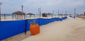 Het grote oranje plastiek kan met droog dichtbij blauwe omheining op het strand planten stock afbeelding