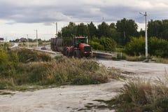 Het grote rode tractor drijven op een landelijke weg Royalty-vrije Stock Foto