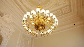 Het grote ronde gouden antieke kroonluchter hangen op het plafond stock videobeelden