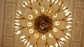 Het grote ronde gouden antieke kroonluchter hangen op het plafond stock footage