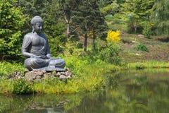 Het grote standbeeld van Boedha naast de tuinvijver Stock Afbeelding