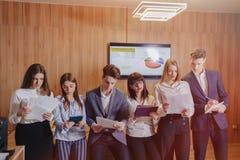 Het grote team van mensen werkt bij ??n lijst voor laptops, tabletten en documenten, aan de achtergrond een grote Televisie op ee stock foto