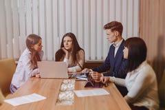 Het grote team van mensen werkt bij ??n lijst voor laptops, tabletten en documenten, aan de achtergrond een grote Televisie op ee stock fotografie