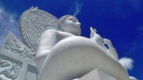 Het grote witte beeldhouwwerk van Boedha onder blauwe hemel en witte wolk Stock Afbeeldingen